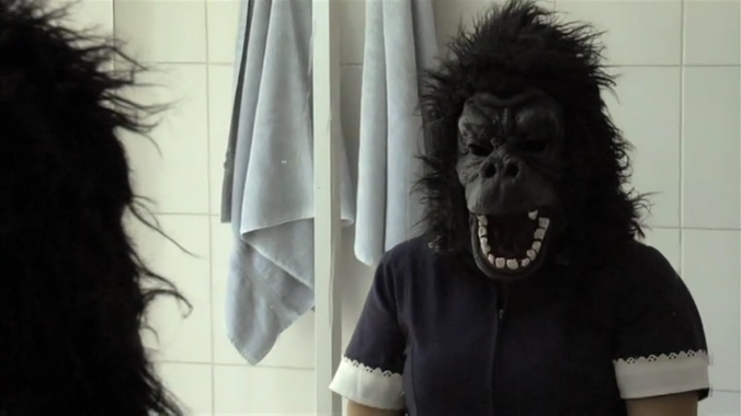 4. Raquel tries on the kids' gorilla mask in the mirror
